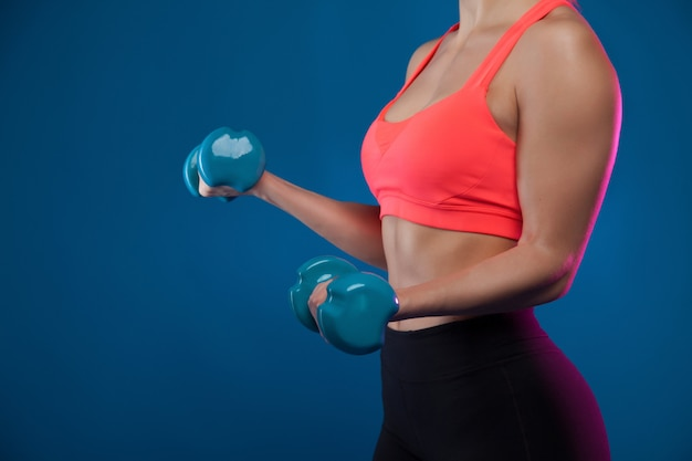 A young blond sporty girl holds a dumbbell in her hands, shakes a muscular.