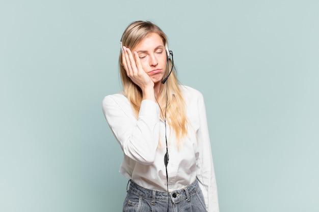 面倒で退屈で退屈な仕事をした後、退屈でイライラして眠くなる若い金髪のテレマーケターの女性が顔を手で持っている