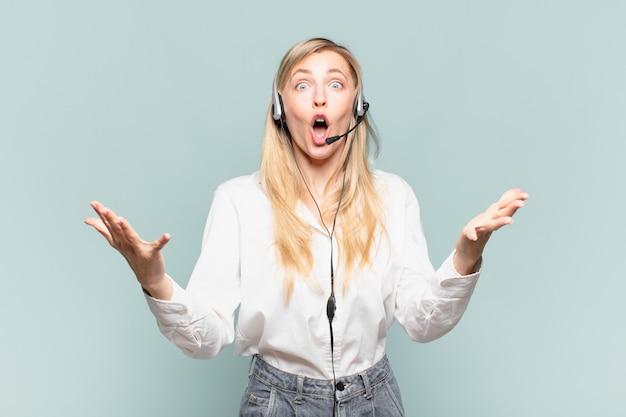 若い金髪のテレマーケティングの女性は、ストレスと恐怖の表情で、非常にショックを受け、驚き、不安とパニックを感じています