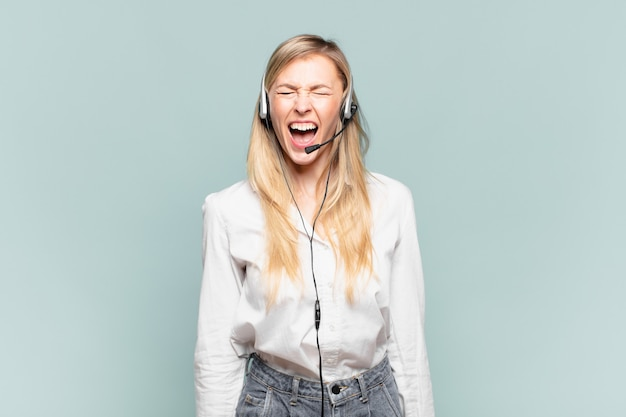 Молодая белокурая женщина-телемаркетер агрессивно кричит, выглядит очень сердитой, расстроенной, возмущенной или раздраженной, кричит нет
