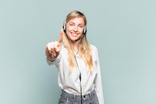 Молодая белокурая женщина-телемаркетер улыбается и выглядит дружелюбно, показывает номер один или первый с рукой вперед, отсчитывая