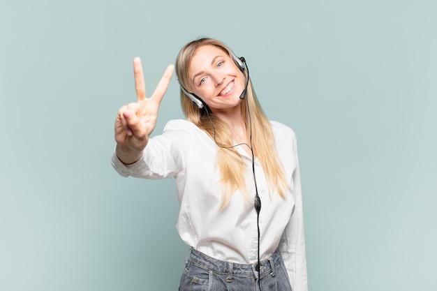 Молодая белокурая женщина-телемаркетер улыбается и выглядит дружелюбно, показывает номер два или секунду рукой вперед, отсчитывая
