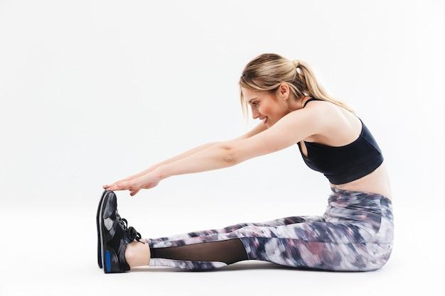 운동복을 입은 20대 젊은 금발 여성이 흰 벽에 격리된 에어로빅을 하는 동안 몸을 스트레칭하고 운동을 하고 있다