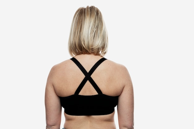 Young blond woman in a black sports top. back view. isolated on white background.