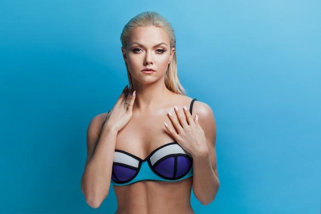 Young blond woman in blue bikini on blue.