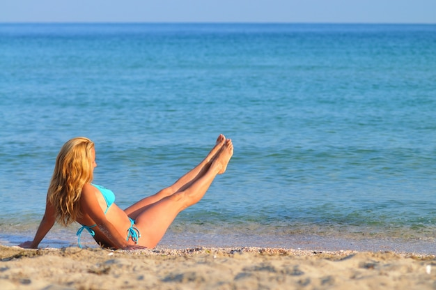 Young blond woman in blue bikini sitting on sea edge with her legs raised