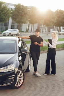 Young blond woman consultant shows the customer the car outdoors. a man buys a car. test drive a new car.