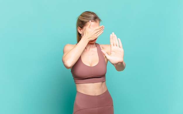 Young blond woman covering face with hand and putting other hand up front to stop camera, refusing photos or pictures. sport concept