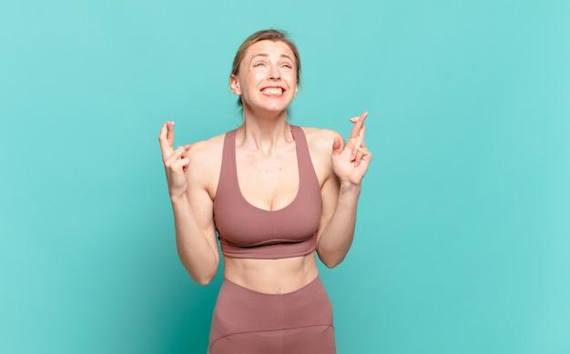 젊은 금발 여성이 걱정스럽게 손가락을 교차하고 걱정스러운 표정으로 행운을 바라고 있습니다. 스포츠 개념