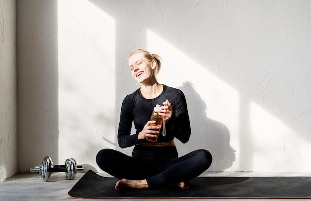 Young blond woman doing yoga or meditating at home drinking water