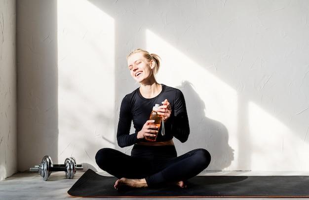 ヨガをしている、または自宅で水を飲んで瞑想している若いブロンドの女性