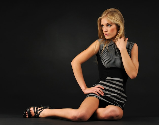 Young blond woman in dress and shoes sitting on floor over dark background