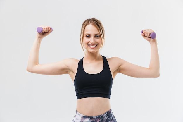 운동복을 입은 젊은 금발 여성이 흰색 벽에 격리된 체육관에서 운동하는 동안 아령으로 운동을 하고 있습니다.