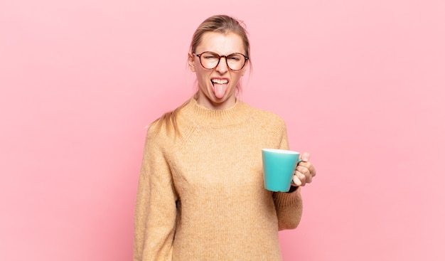 Young blond woman feeling disgusted and irritated, sticking tongue out, disliking something nasty and yucky. coffee concept