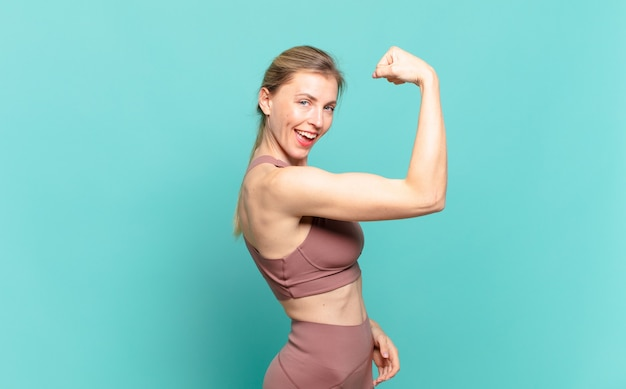 若いブロンドの女性は、幸せで、満足していて、力強く、屈曲したフィット感と筋肉の上腕二頭筋を感じ、ジムの後で強く見えます。スポーツコンセプト