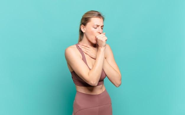 인후염과 독감 증상으로 아프고 입을 가리고 기침하는 젊은 금발 여성. 스포츠 개념