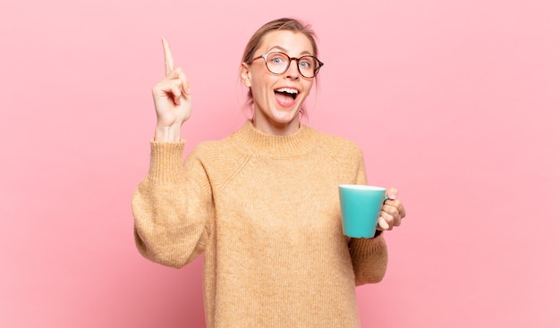 생각을 깨달은 후 행복하고 흥분된 천재 같은 느낌의 젊은 금발 여성, 유레카 유레카!. 커피 개념