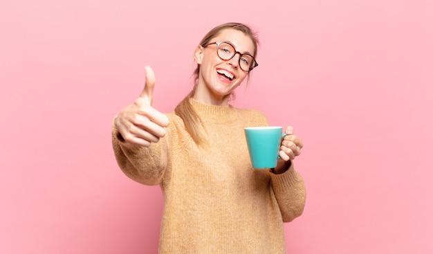 若いブロンドの女性は、誇り、のんき、自信を持って幸せを感じ、親指を立てて前向きに笑っています。コーヒーのコンセプト