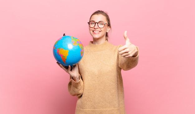 자랑스럽고 평온하고 자신감 있고 행복하다고 느끼는 금발의 젊은 여성은 엄지손가락을 치켜들고 긍정적으로 웃고 있습니다. 세계 개념