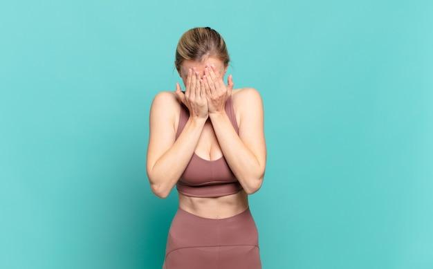 젊은 금발 여성은 슬프고, 좌절하고, 긴장하고, 우울해하며, 두 손으로 얼굴을 가리고 울고 있습니다. 스포츠 개념