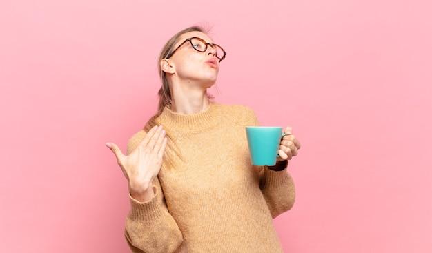 若いブロンドの女性は、ストレス、不安、疲れ、欲求不満を感じ、シャツの首を引っ張って、問題で欲求不満に見えます。コーヒーのコンセプト