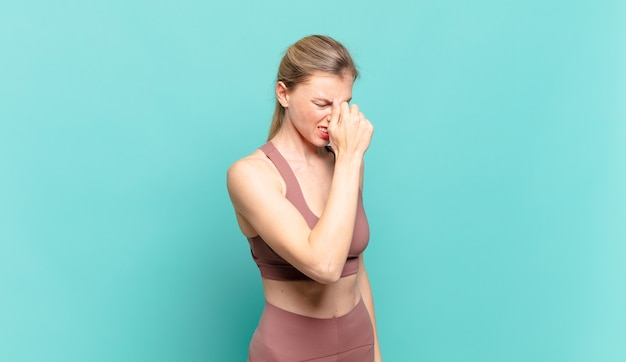 젊은 금발 여성은 스트레스, 불행, 좌절감을 느끼고 이마를 만지고 심한 두통의 편두통을 앓고 있습니다. 스포츠 개념