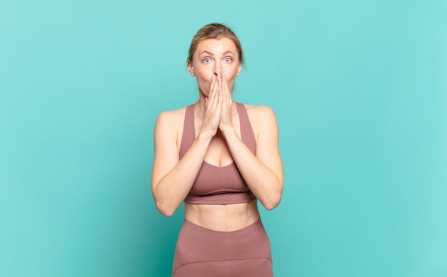Young blond woman feeling worried, upset and scared, covering mouth with hands, looking anxious and having messed up. sport concept