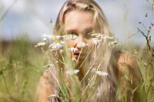 Young blond woman in a field with camomiles. rest on a summer day. close-up.