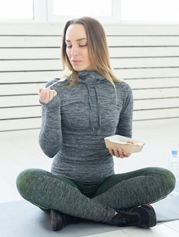 Young blond woman in fitness wear, with vegetarian healthy food, sitting on floor