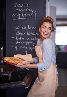 パイを保持している若いブロンドの女性