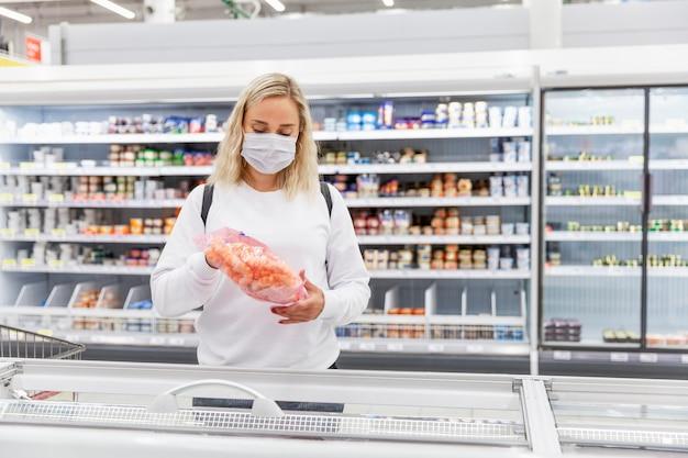 冷凍食品部門の医療マスクの若いブロンドの女性。パンデミック時の健康と適切な栄養。