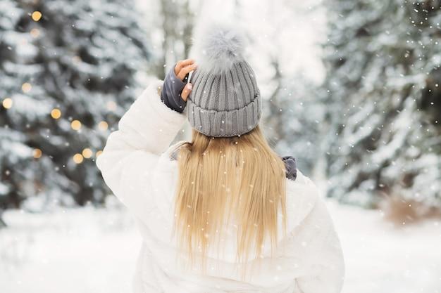 雪の降る天気で森を見ている白いコートを着た若いブロンドの女性