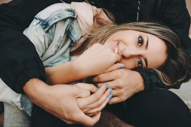 단계에 앉아 카메라에 미소 작물 남자의 팔에 젊은 금발 여자