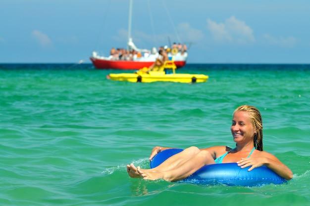 海の水泳サークルに乗って、晴れた夏の日に笑顔の青いビキニの若いブロンドの女性。幸福、休暇、自由の概念