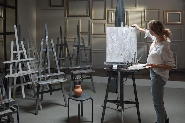 Молодая блондинка женщина в повседневной одежде держит цветовую палитру, стоя перед картиной на мольберте и рисует в студии