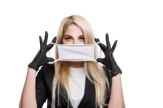 医療マスクと手袋の若いブロンドの女性。白い背景で隔離