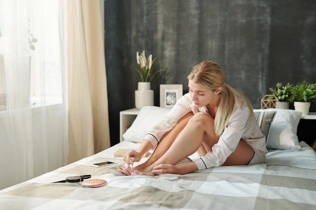 ベッドに座って、朝にマニキュアで足指の爪を描くシルクパジャマの若いブロンドの女性