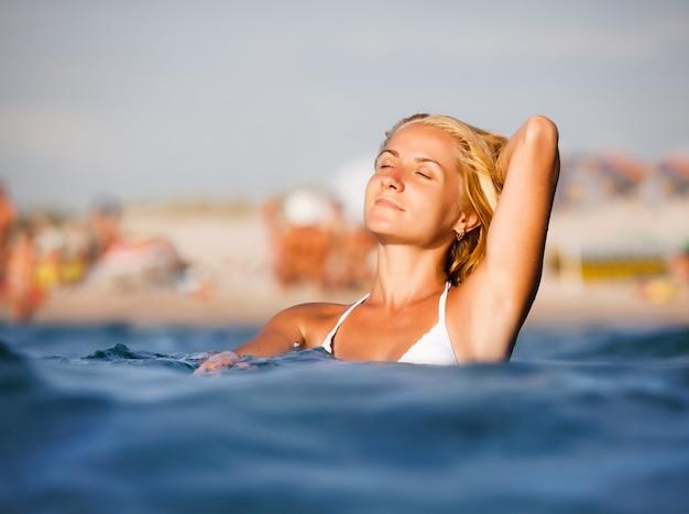 아직도 바닷물에 서서 배경에서 해변과 화창한 여름 날에 햇빛을 즐기는 흰색 비키니에 젊은 금발 여자. 가족 휴가 및 여행 개념
