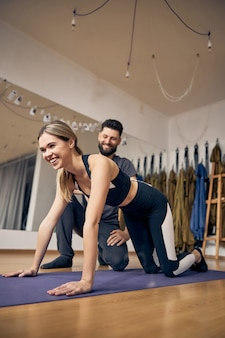 Young blond woman laughing while doing exercise with the help pf experienced instructor in the gym