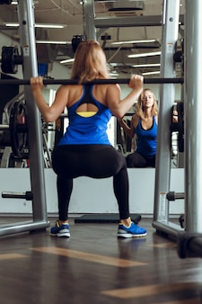 Young blond woman lifting barbells in the gym