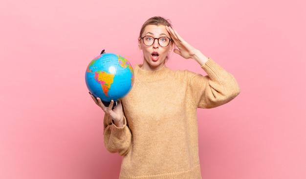 幸せそうに見えて、驚いて、驚いて、微笑んで、驚くべきそして信じられないほどの良いニュースを実現している若いブロンドの女性。世界のコンセプト