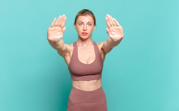 真面目で、不幸で、怒って、不機嫌そうに見える若いブロンドの女性は、立ち入りを禁じているか、両方の手のひらを開いて停止すると言っています。スポーツコンセプト