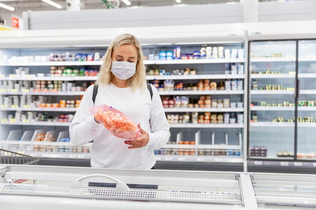 Young blond woman in a medical mask in the frozen food department. health and proper nutrition during a pandemic.