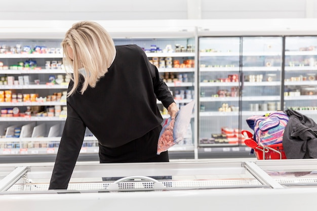 Young blond woman in a medical mask in the supermarket chooses products. coronavirus pandemic.