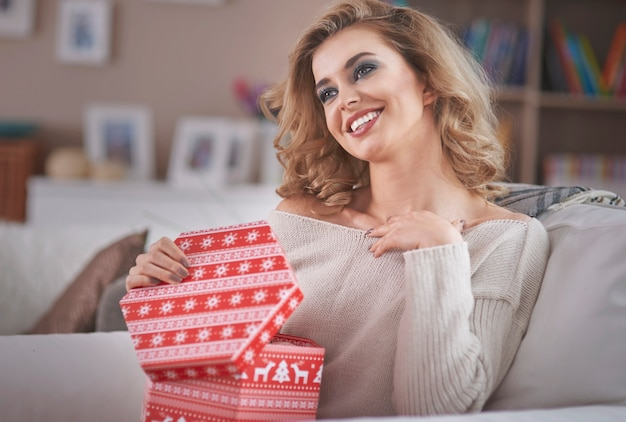 크리스마스 선물을 여는 젊은 금발 여자