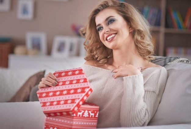Giovane donna bionda che apre un regalo di natale