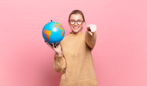 당신을 선택하는 만족스럽고 자신감 있고 친절한 미소로 카메라를 가리키는 젊은 금발 여성. 세계 개념