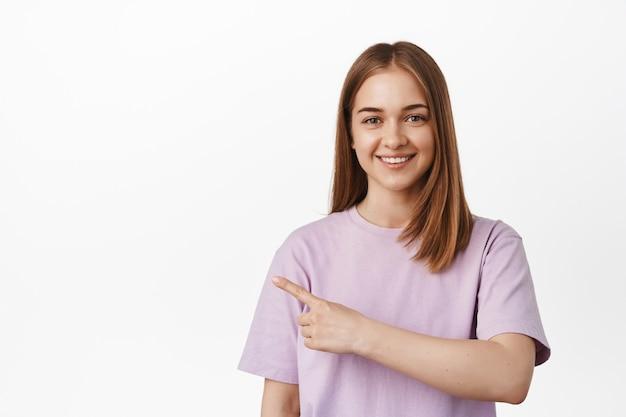 左の指を指して、幸せな笑みを浮かべて、白い壁にtシャツで立っている若いブロンドの女性