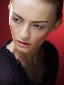 Молодая блондинка женщина позирует на красном фоне, концепция красоты