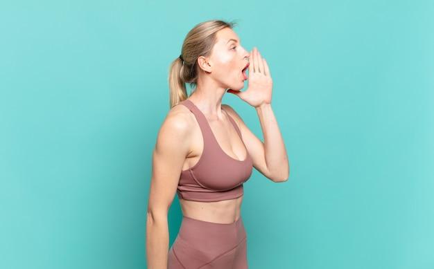 Вид профиля молодой белокурой женщины, выглядящий счастливым и взволнованным, кричащим и призывающим скопировать пространство на стороне. спортивная концепция
